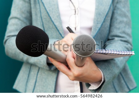 Female journalist at press conference, writing notes, holding microphone #564982426