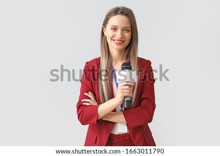 Female journalist on light background Foto stock ©
