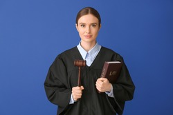 Female judge with book on color background
