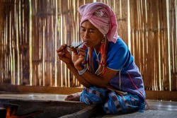 Female karen hill tribe is smoking tobacco pipe traditional in the cottage of northern Thailand at  Mae Klang Luang, Mae Chaem, Chiang Mai Province