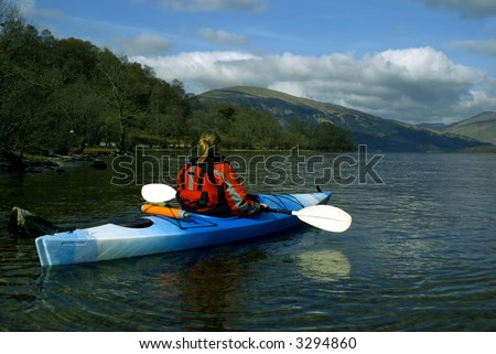 Female kayaker paddling away from the viewer on Loch Lomond with Ben Lomond mountain in the background
