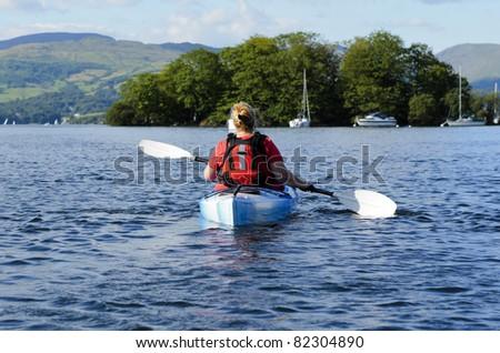 Female kayaking on Lake Windermere in Lake District National Park Cumbria UK
