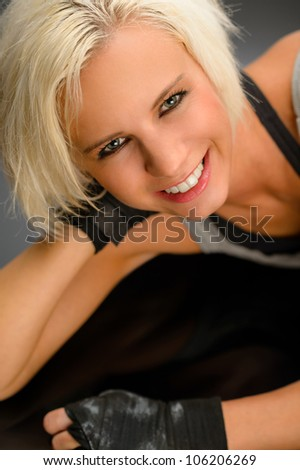 Female kick boxer laying down on black floor close-up portrait