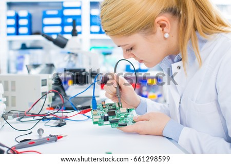 Female laboratory assistant Repairs PCB module for CNC robotics. Measurement of the parameters of the electronic system in the laboratory
