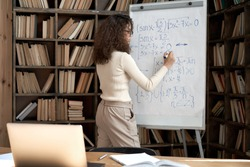 Female latin indian math school teacher or student writing equation on whiteboard in classroom. Virtual live remote teaching concept. Distance online education exam preparation elearning course.