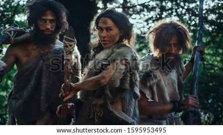 Female Leader and Two Primeval Cavemen Warriors Threat Enemy with Stone Tipped Spear, Scream, Defending Their Cave and Territory in the Prehistoric Times. Neanderthals / Homo Sapiens Tribe