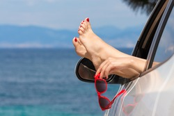 Female legs and hand holding red sunglasses through car window against blue sea background. Travel and summer vacation concepts.