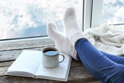 Female legs and hot drink on windowsill