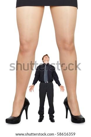 Female legs and little amazed man on white background