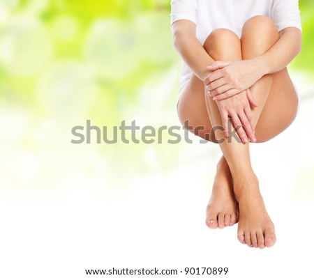 female legs being massaged over green spring background with white copyspace to place your advertisement- spa and healthcare concept