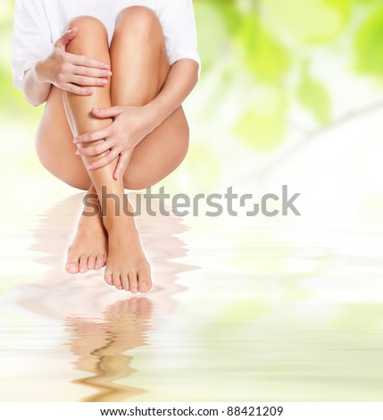 female legs being massaged under clean water waves over green spring background - spa and healthcare concept - stock photo