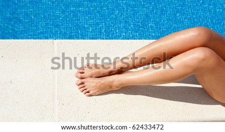 Female legs by the swimming pool