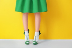 Female legs in green high heel shoes and socks on color background