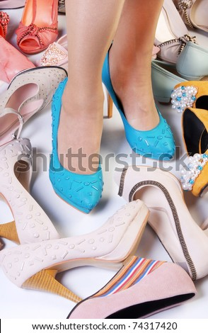 Female legs in high heels and a number of different high-heeled shoes - stock photo