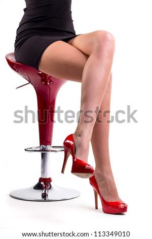 female legs in high heels sitting on chair