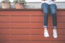 Female legs in jeans and white sneakers hanging from a wooden wall on a sunny summer day. Woman relaxes by the sitting on the edge of a wooden.