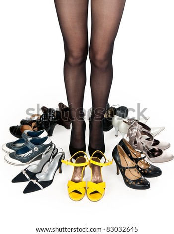 female legs in pantyhose, surrounded by stylish shoes in the studio on a white background