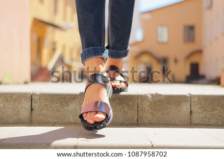 Female legs in sandals descending the stairs in the city