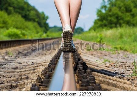 Stock Photo female legs in sneakers on the rail of the railway