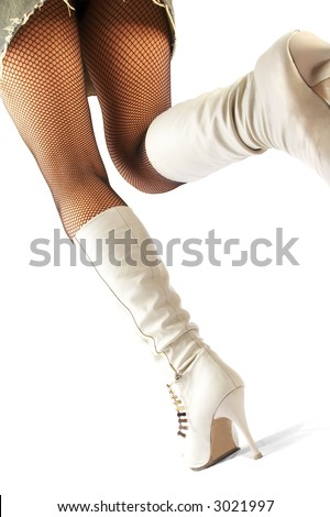 Female legs in stockings and white boots.