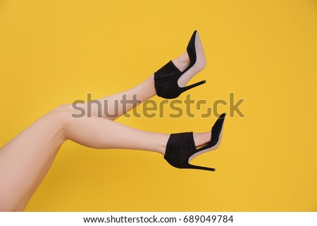 Female legs in stylish shoes on color background #689049784