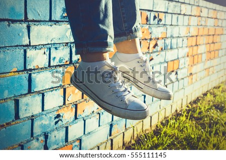 Female legs in white canvas sneakers and jeans dangling from a blue brick wall on a sunny summer day #555111145