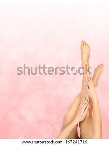 female legs massage with hands over pink bokeh background - spa and beauty concept