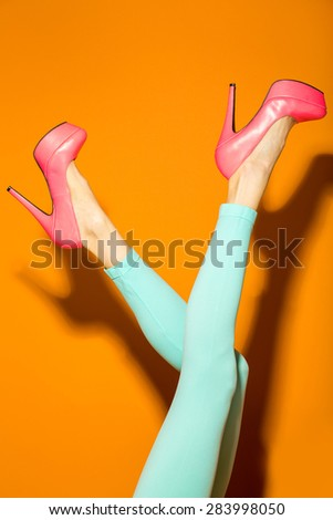 Female legs wearing high heels over orange background #283998050