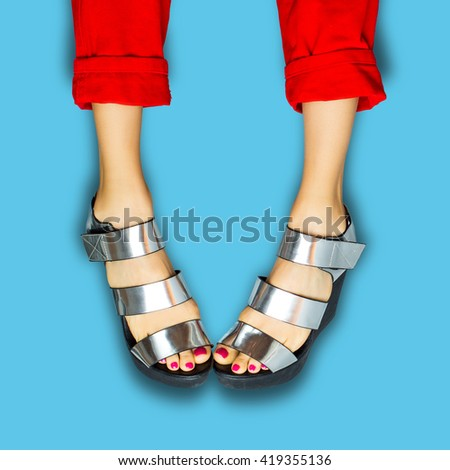 Female legs wearing summer hights over blue background