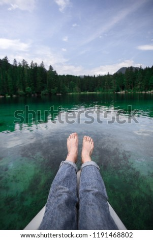 Female legs with bare feet in blue salvage denim jeans stretched out from vintage green rowing boat, that glides through crystal clear see through turquoise waters of mountain alpine lake, lifestyle