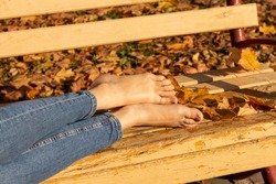Female legs with bare feet on a bench in the park in autumn.
