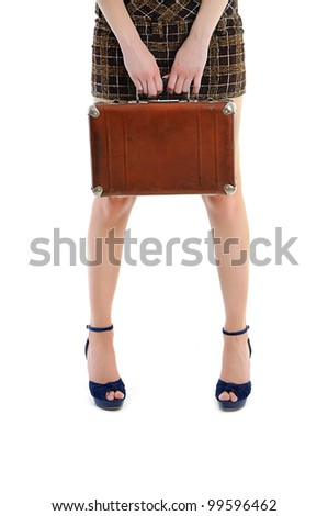 female legs  with hands holding vintage brown case - travel and vacation concept