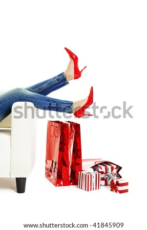 Female legs with sexy red shoes over christmas presents - stock photo