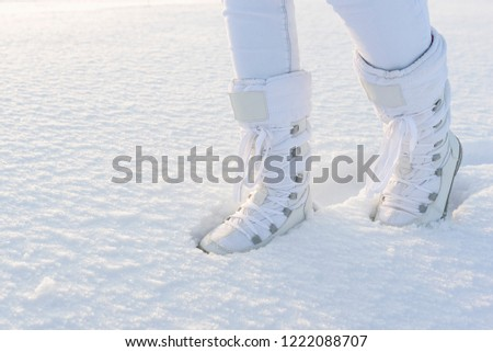 Female legs with white snow boots on, walking by the snow cover in sunlight. Winter background. #1222088707