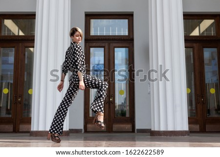 female lessons of lifestyle posing in a standing pose. beautiful European girl in a black suit with white spots in high heels, pants and a shirt. Long legs lift high. Leg stretch