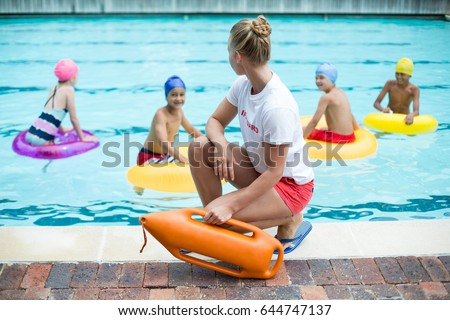 Female lifeguard holding rescue can while children swimming in pool Stockfoto ©