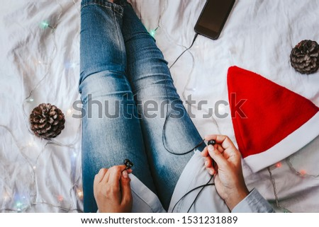 Female listening to music in bed. Pine tree cones, Santa Claus cap and smartphone with earphones near the legs of female. Christmas holidays. X-mas morning in a cosy bedroom. #1531231889