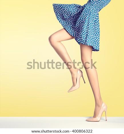 Female long legs in fashion skirt and high heels. Female sexy legs, stylish dress, glamour fashion heels, model pose. Creative elegant summer female look. Fashion trendy female outfit, fashion shoes