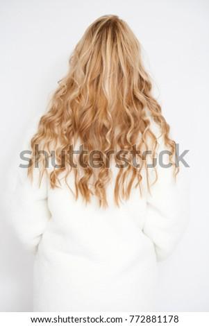 Female Long wavy blonde hair, rear view, studio wall background