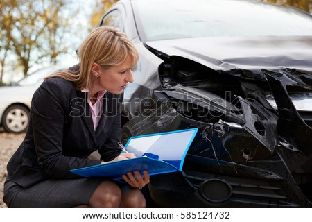 Female Loss Adjuster Writing Report On Damaged Car