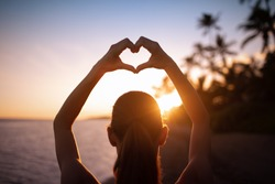 Female making heart hand symboled against beautiful beach sunset sky.