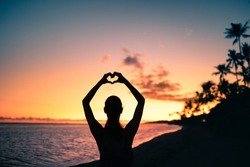 Female making heart shape hand standing on a beautiful tropical beach at sunset. People travel, in love with nature concept.