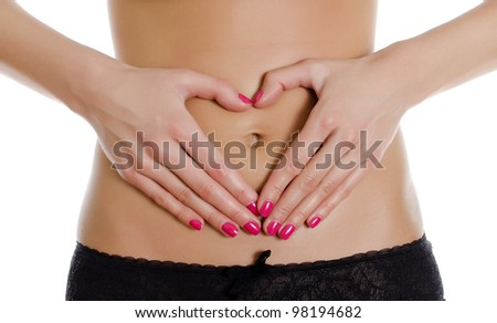Female making heart shape with her hands on her belly. Isolated on white.