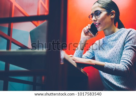 Female manager having mobile phone conversation sitting in noise insulance booth in office getting information,businesswoman talking on smartphone in silence of cabin using laptop for checking data