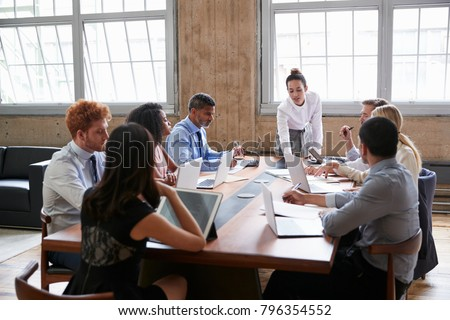 Female manager leans while addressing team at board meeting