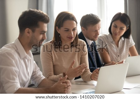 Female manager mentor teach help male intern trainee new employee explain online strategy on laptop at group meeting, focused business woman talk to colleague client work together cooperate in office