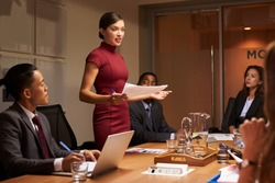 Female manager  standing with documents at business meeting