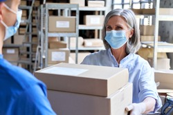 Female manager worker wearing face mask holding fast drop shipping safe delivery packages giving parcels shipment boxes to male courier taking ecommerce orders to deliver in warehouse storage.