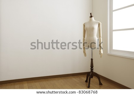 Female mannequin in white room.
