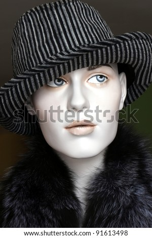 female mannequin wearing a fedora hat and fur collar